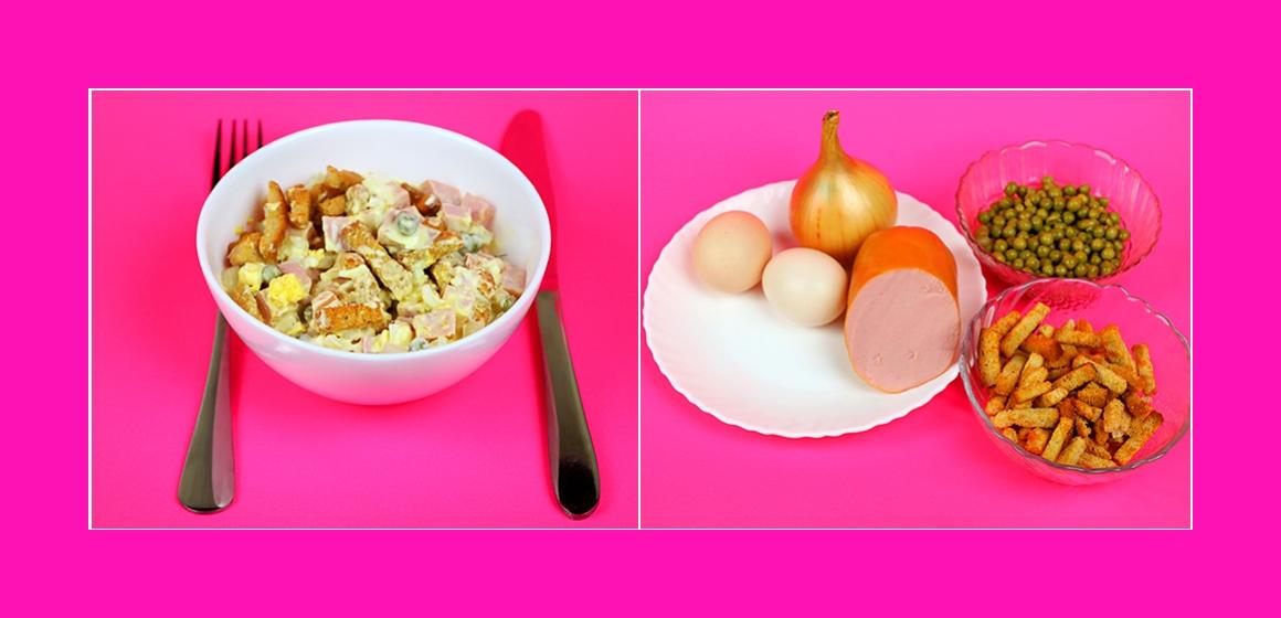 Leckerer Salat mit Kochwurst, Croutons, Eiern und grünen Erbsen